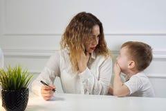 Wenig Junge stoppt seine Mutter, um zu arbeiten, w?hrend sie Telefon an ihrem Arbeitsplatz im B?ro nennt Berufst?tige Mutter stockbild