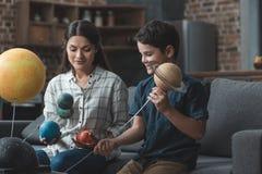 Wenig Junge und seine Mutter, die ein Sonnensystemmodell konstruieren lizenzfreies stockfoto