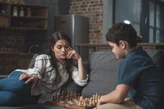 Wenig Junge und seine junge Mutter, die Schach auf Couch spielen stockfotos