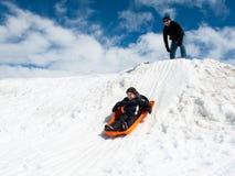 Wenig Jungen- und Vatifahrt auf einen schneebedeckten Hügel lizenzfreies stockfoto