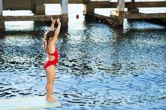 Wenig kaukasische 6 Jahre alte Mädchen, die für Sprung in das Meer vom Sprungbrett sich vorbereiten Lizenzfreie Stockbilder