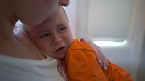 Wenig Kind im Flugzeug schreit, Mutter beruhigt ihn unten in der Zeitlupe stock video footage