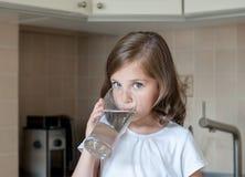 Wenig Kind trinkt Trinkwasser zu Hause, Abschluss oben Kaukasisches nettes Mädchen mit dem langen Haar hält ein Wasserglas in ihr lizenzfreie stockbilder