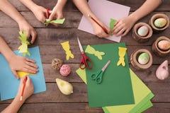 Wenig Kinder, die bei Tisch Ostern-Dekorationen machen lizenzfreie stockfotografie