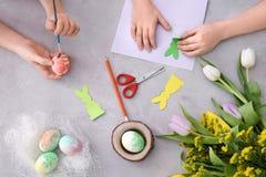 Wenig Kinder, die Eier malen und bei Tisch Ostern-Dekorationen machen stockfotos