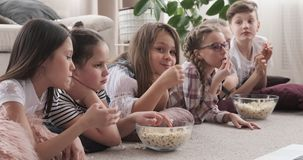 Wenig Kinder, die Film aufpassen und Popcorn essen stock video
