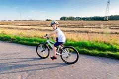 Wenig Kinderjunge im wei?en Sturzhelm, der sein Fahrrad f?hrt lizenzfreie stockbilder