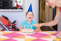 Wenig Kinderlachen und -frau Kerzen auf Geburtstag cak beleuchtend Lizenzfreies Stockbild