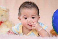 Wenig Kinderspiel mit ihren Zähnen und Mund auf weichem Bett Lizenzfreie Stockfotografie