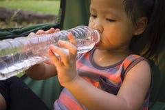 Wenig Kindertrinkwasser von der Flasche im gr?nen Park stockbilder