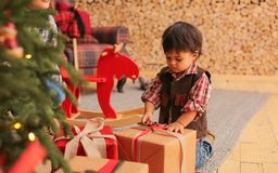 Wenig Kleinkind packt Geschenke aus stockfotografie