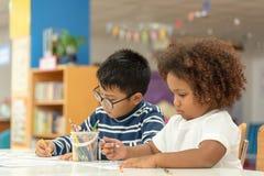 Wenig Kleinkindmädchen und -junge, die zusammen zeichnen Asiatischer Junge und afrikanisches M?dchen mischen, in der Vorschule- K lizenzfreie stockfotografie