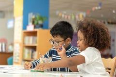 Wenig Kleinkindm?dchen und -junge, die zusammen zeichnen Asiatischer Junge und afrikanisches M?dchen mischen, in der Vorschule- K lizenzfreie stockbilder
