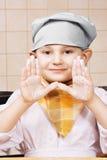 Wenig Koch, der die Hände befleckt mit Mehl zeigt lizenzfreie stockfotografie