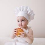 Wenig Koch isst einen Apfel Stockfoto