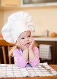 Wenig kochen das Mädchen, das an der Küchetabellenaufwartung sitzt Lizenzfreie Stockfotos