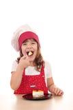 Wenig Kochmädchen essen Kuchen Lizenzfreies Stockfoto