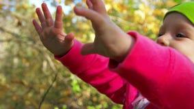 Wenig lächelndes Mädchen dehnt ihre Arme zu den Händen der Mutter oder des Vatis aus stock footage