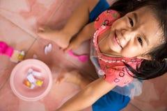 Wenig Lächelnmädchen, das Spielwaren auf dem Boden spielt Stockfoto
