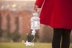 Wenig Laterne mit magischem Beleuchtungsgriff durch eine Frau in einem Rot Lizenzfreies Stockfoto