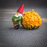 Wenig lustige Gnomskulptur lehnt sich auf dem orange Kürbis Stockfotos