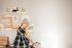 Wenig lustiges Mädchen, das nahe grauer Chistmas-Wand sitzt lizenzfreie stockbilder