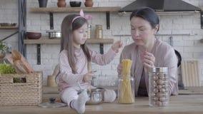 Wenig lustiges Mädchen, das am Tisch hilft ihrer Großmutter, Nudeln zu kochen sitzt Ältere Frau, die nahe der Tabelle steht stock video