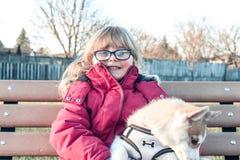 Wenig Mädchen alterte 3 bis 5 Griffe ein Welpe auf ihren Armen, sibirischer Husky stockbilder