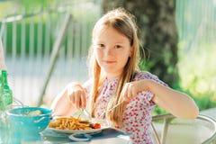 Wenig Mädchen, das Abendessen auf einer Terrasse isst lizenzfreies stockfoto