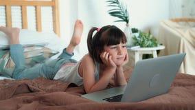 Wenig Mädchen, das auf Bett und aufpassender Karikatur auf Laptop in ihrem Raum, Zeitlupe liegt stock video footage