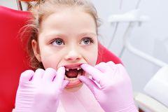 Wenig Mädchen, das auf zahnmedizinischem Stuhl im pädiatrischen Zahnarztbüro sitzt stockfotos