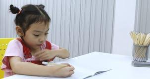 Wenig Mädchen, das bewusst irgendeine Karikatur zeichnet stock video footage