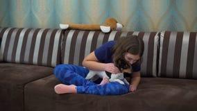 Wenig Mädchen, das den Hund auf dem Sofa umarmt stock video
