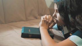 Wenig Mädchen, das in der Nacht betet Wenig Mädchenhandbeten heilige Bibel des kleinen Mädchens betet mit Bibel in ihren Händen stock video