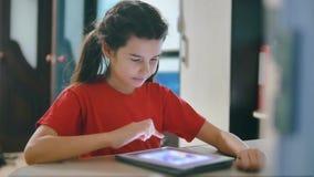 Wenig Mädchen, das digitale Tablette spielt kleines Mädchen, das am Tisch spielt digitale Tablette im on-line-Spielsocial media s stock video