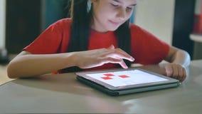 Wenig Mädchen, das digitale Tablette spielt kleines Mädchen, welches am Lebensstil die Tabelle spielt digitale Tablette in den on stock video footage