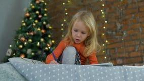 Wenig Mädchen, das ein Bild nahe dem Weihnachtsbaum zeichnet stock video
