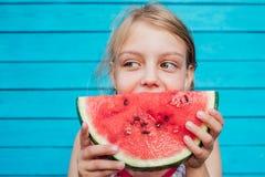 Wenig Mädchen, das eine reife saftige Wassermelone über blauem Plankenwandhintergrund isst lizenzfreie stockfotos