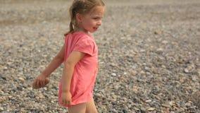 Wenig Mädchen, das in einem Strandzelt durch das Meer spielt