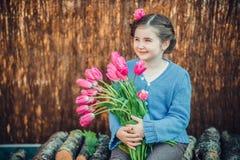 Wenig Mädchen, das glücklich mit rosa Blumen lächelt stockbild