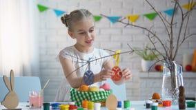 Wenig Mädchen, das handgemachte Spielzeugeier auf Baumasten, Ostern-Dekoration hängt stock video