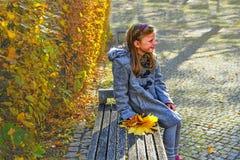 Wenig Mädchen, das Retro- Mantel trägt und auf Bank im Park im Herbst sitzt Kleines Mädchen hält bunten Herbstlaub Herbst concep stockbild