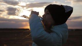 Wenig Mädchen, das Süßwasser von der Plastikflasche mit Sonnenunterganghintergrund trinkt Zu Ihren Durst löschen stock video footage
