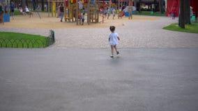 Wenig Mädchen, das am Spielplatz geht Kind, das drau?en im Sommer spielt Gl?ckliche Kindheit stock video
