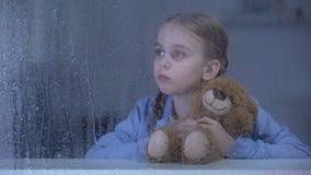 Wenig Mädchen, das Teddybären umarmt und durch Fenster im regnerischen Wetter schaut stock footage