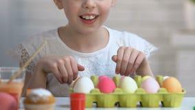 Wenig Mädchen, das von unterhalb der Tabelle wie Kaninchen scheint, hell gefärbte Eier zu genießen stock video