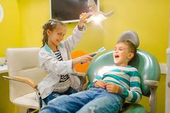 Wenig Mädchen in der Uniform, die Zahnarzt, Spielzimmer spielt stockfotografie