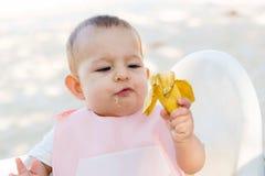 Wenig Mädchen des achtmonatigen Babys isst Mit Erstaunen und Bewunderung betrachtet Baby eine Banane auf dem Strand lizenzfreies stockbild