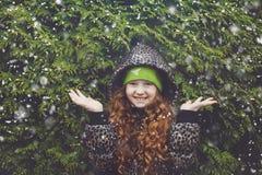 Wenig Mädchen des gelockten Haares nahe grünem Winterbaum lizenzfreies stockfoto