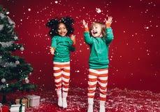 Wenig Mädchen, die mit künstlichen Schneeflocken spielen lizenzfreie stockbilder